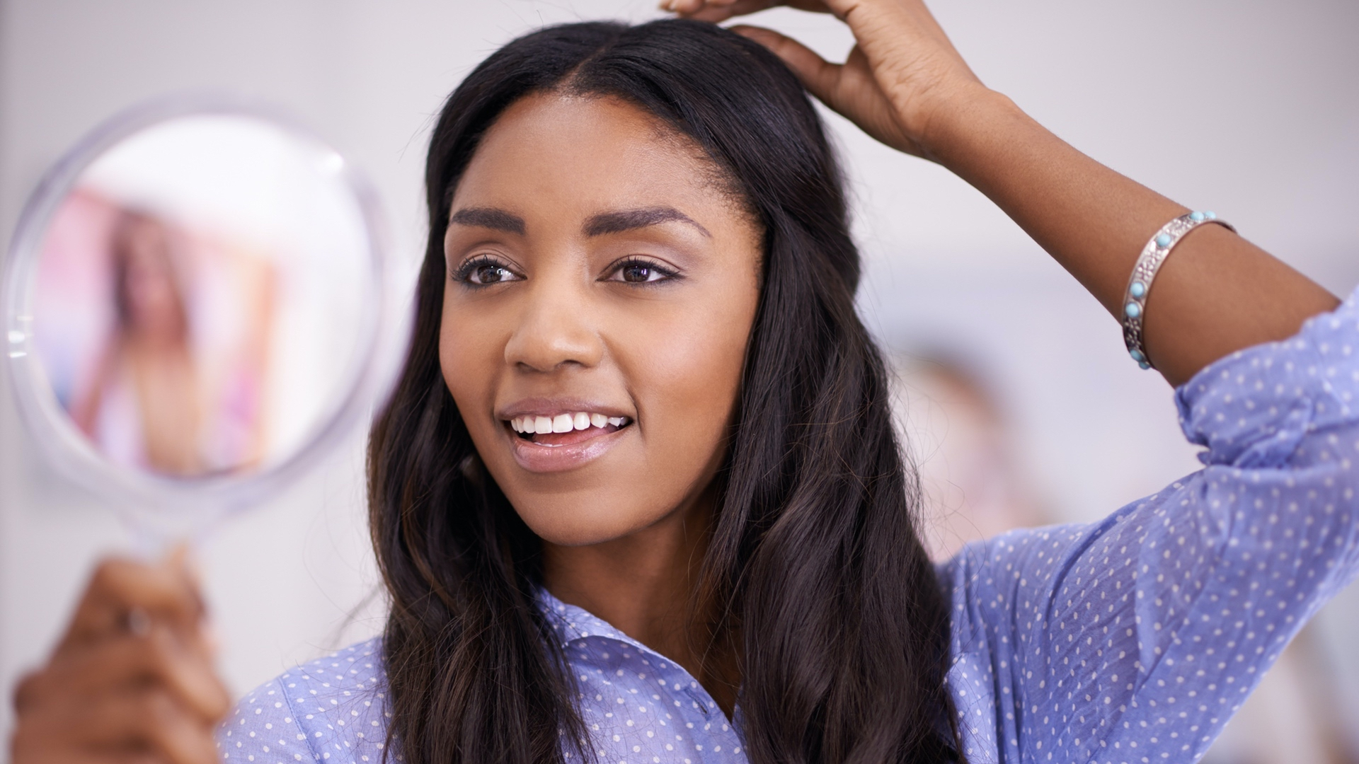 Girl looking happy with hand on her head and Brazilian Loose Wave Hair Extensions