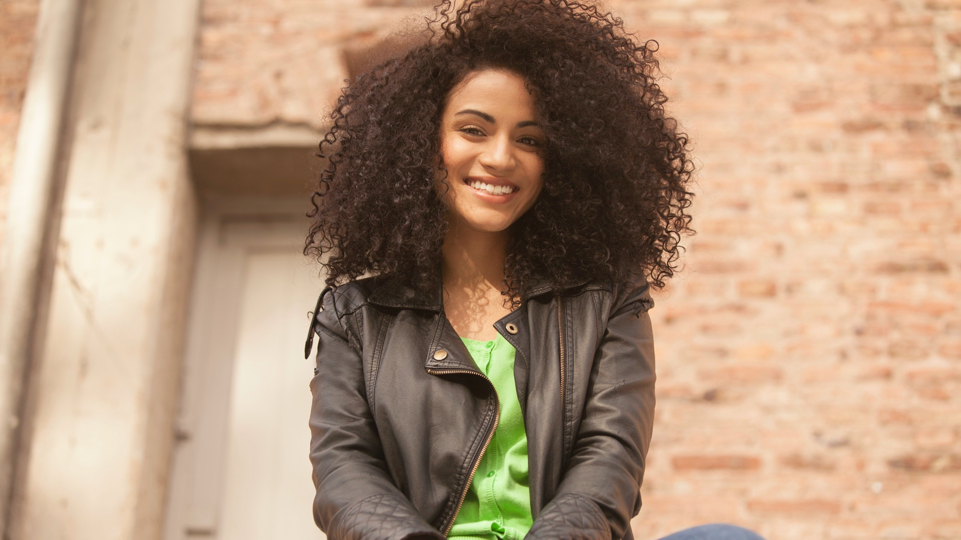 Girl smiling with Brazilian Kinky Curly Hair Extensions